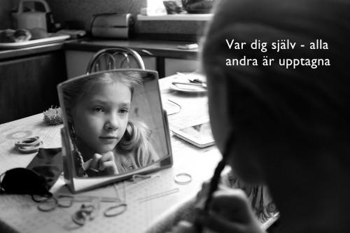 Ansiktee som ser sig i en spegel
